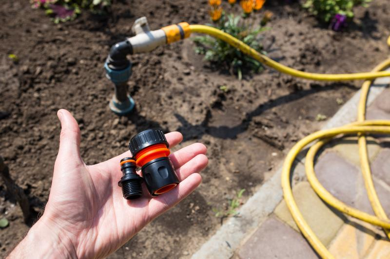 Person hält Steckverbindungen für eine Wassersteckdose in der Hand